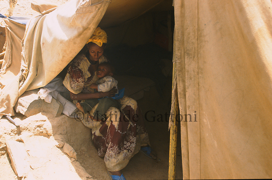 Eritrea - Debub - A mother taking care of her child inside her family tent in an IDP camp. As a result of 30 years of war for independence against Ethiopia (from 1961 to 1991) and another 3 years from 1997 to 2000, there are 50,000 Eritreans currently living in internally displaced (IDP) camps throughout the country. These IDPs have fled three times in the last 10 years, each time because of renewed military conflict. They lived in relatives' homes when lucky enough, but mostly, the fled to the mountains, where they attempted to do what Eritreans do best, survive. Currently there is no Ethiopian occupation in Eritrea, but landmines prevent the IDPs from finally going home. .It is estimated that every Eritrean family lost two or three members to the war which makes the reality of the current emergency situation even more painful for Eritreans worldwide. Currently, the male population has been decreased dramatically, affecting the most fundamental socio-economic systems in the country. Among the refugee population, an overwhelming majority of families are female-headed, severely affecting agricultural production. For, IDPs in particular, 80% of households are female-headed..The unresolved border dispute with Ethiopia remains the most important drawback to Eritrea's socio-economic development, as national resources (human and material) continue to be prioritized for national defense. Eritrea is vulnerable to recurrent droughts and variable weather conditions with potentially negative effects on the 80 percent of the population that depend on agriculture and pastoralism as main sources of livelihood. The situation has been exacerbated by the unresolved border dispute, resulting in economic stagnation, lack of food security and increased susceptibility of the population to various ailments including communicable diseases and malnutrition. .