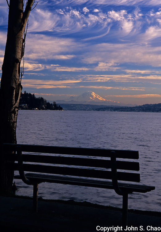 A silhouetted park bench on Lake Washington with a view of Mt. Rainier. Seward Park, Seattle, Washington.