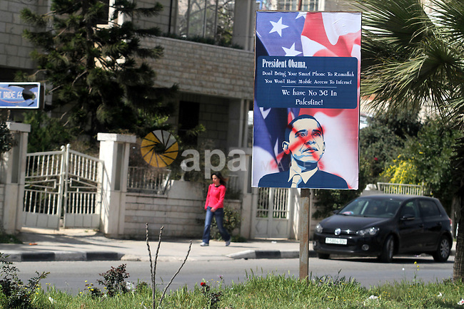A Palestinian woman walks past a posters with a slogan against the upcoming visit of US President Barack Obama to the West Bank city of Ramallah is seen on March 14, 2013, in central Ramallah. Obama's three-day visit to Israel and the Palestinian territories will begin on March 20, in the first official announcement of the much-anticipated visit. Photo by Issam Rimawi