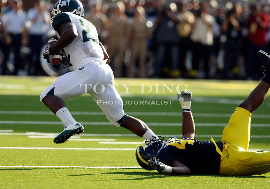 Michigan State running back Larry Caper (22) escapes a tackle from Michigan linebacker Obi Ezeh (45) in the second quarter of an NCAA college football game, Saturday, Oct. 9, 2010, in Ann Arbor, Mich. (AP Photo/Tony Ding)