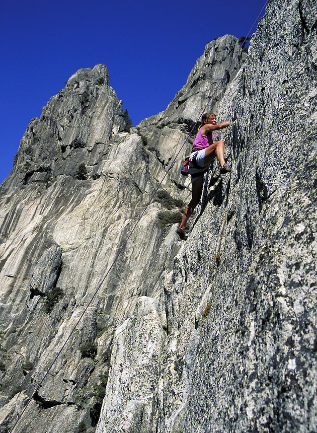 female rock climber climbing on face of granite formation. rock climber. California USA.