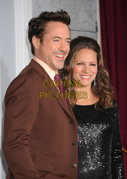 Robert Downey Jr. & Susan Levin .The World Premiere of 'Sherlock Holmes: A Game of Shadows' held at The Village Theatre in Brentwood, California, USA..December 6th, 2011.half length married husband wife black sequins sequined dress pregnant brown suit pink tie blue cardigan .CAP/ROT/TM.©Tony Michaels/Roth Stock/Capital Pictures