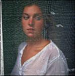 Young woman looking through screen door