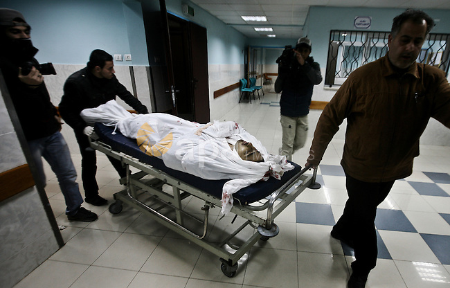 Relatives of Ahmed salem, 22-year-old, look at his body in the morgue of Al-Shifa hospital in Gaza City, on March 11, 2012, following a fresh Israeli air raid, bringing the death toll from strikes since March 10 to 17 and dashing Hamas hopes of restoring a tacit truce. Photo by Ali Jadallah