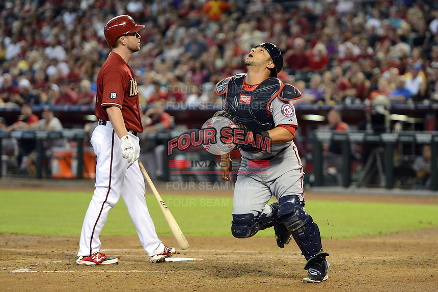 Washington Nationals catcher Jhonatan Solano (23) looks for a pop up foul ball as Aaron Hill stands at the plate during a game against the Arizona Diamondbacks at Chase Field on September 29, 2013 in Phoenix, Arizona.  Arizona defeated Washington 3-2.  (Mike Janes/Four Seam Images)