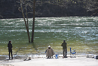HIGH-WATER FLOW<br />Anglers fish on the White River below  Beaver Dam on Saturday March 21 2020 during high flows with the dam's seven floodgates open. Each floodgate is open 1.5 feet to lower the water level of Beaver Lake after heavy rain last week. Some 5.3 million gallons of water per minute, or 12,000 cubic feet per second, are flowing through the dam, according to Army Corps of Engineers information. The dam is located on Arkansas 187 about 25 miles northeast of Rogers or 9 miles west of Eureka Springs. Beaver Lake is the drinking water source for most of Northwest Arkansas and beyond. Go to nwaonline.com/200322Daily/ to see more photos.<br />(NWA Democrat-Gazette/Flip Putthoff)