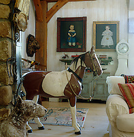 A 'photo pony' that was used for photo shoots and can be dismantled and a concrete bull terrier by Robert Young antiques stand by the fireplace