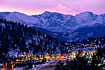 Christmas lights brighten downtown Estes Park with Rocky Mountain National Park as a backdrop, Colorado.
