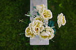 "Cloth flowers stand on the grave marker of Denise McNair in Elmwood Cemetery in Birmingham, Alabama. She was one of four girls killed in a bombing at 16th Street Baptist Church September 15, 1963. The tombstone is inscribed with ""She loved all--but a mad bomber hated her kind."""
