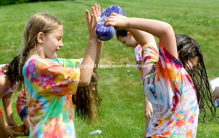 BETHLEHEM CT. 12 June 2015-061215SV06-From left, Samantha Molzon, 9, of Bethlehem grabs a water soaked sponge from Ava Witte, 10, of Woodbury in a relay race during field day at Bethlehem Elementary School in Bethlehem Friday. <br /> Steven Valenti Republican-American