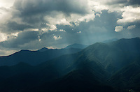 Sunlight streaming through clouds at the edge of the Japan Alps