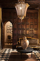 The wood panelled lobby has a romantic and intimate feel with a massive Moroccan ceiling lantern, leather and gilt Louis XVI sofa and a black and white tiled floor