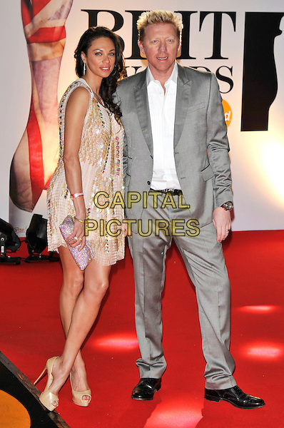 """SHARLEY """"LILY"""" KERSSENBERG BECKER & BORIS BECKER .The BRIT Awards 2011 - Arrivals at the O2 Arena, London, England, UK, .February 15th, 2011..brits full length husband wife grey gray suit couple gold dress white shirt platform peep toe shoes .CAP/PL.©Phil Loftus/Capital Pictures."""
