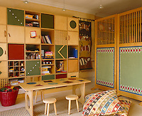 This children's play area is dominated by a wall of keeping holes and square cupboards with a wooden screen which separates it from the kitchen