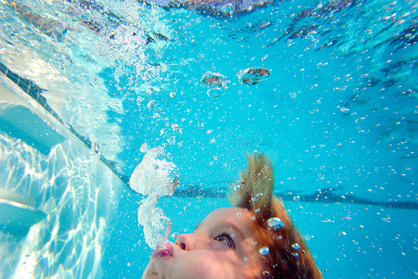 A young boy swims in a swimming pool on a summer day in San Diego, California.