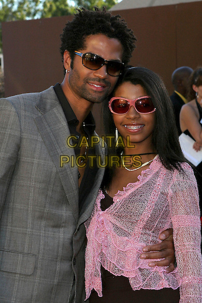 ERIC BENET & INDIA.2005 Soul Train Lady of Soul Awards - Arrivals held at the Pasadena Civic Center, Pasadena,  CA..September 7th, 2005.Photo credit: JW.half length sunglasses shades stubble facial hair unbuttoned daughter father family braces teeth pink .www.capitalpictures.com.sales@capitalpictures.com.© Capital Pictures.