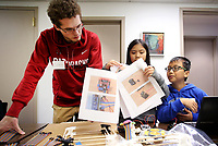NWA Democrat-Gazette/DAVID GOTTSCHALK  Canon Reeves (from left), an instructor with Modbot, works with Lily and Luu Adler Monday, March 19, 2018 in the Nerdies Spring Break Session Build a Modbot Robot at the NWA Fab Lab in Fayetteville. The three day camp for students ages 9-15 is a partnership between the New Design School and NWA Fab Lab. The students will build, wire, program and then bring the modbot robots home. The students also learned the essentials of soldering and Arduino Programming.