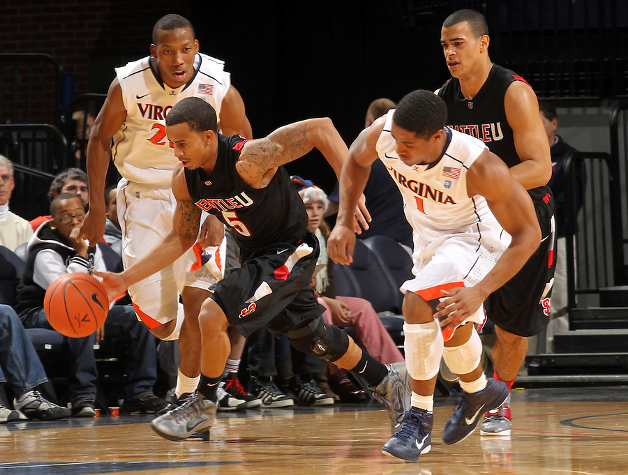 Dec. 22, 2010; Charlottesville, VA, USA; Seattle Redhawks guard Garrett Lever (1) drives past Virginia Cavaliers forward Akil Mitchell (25) and Virginia Cavaliers guard Jontel Evans (1) after stealing the ball during the game at the John Paul Jones Arena. Mandatory Credit: Andrew Shurtleff