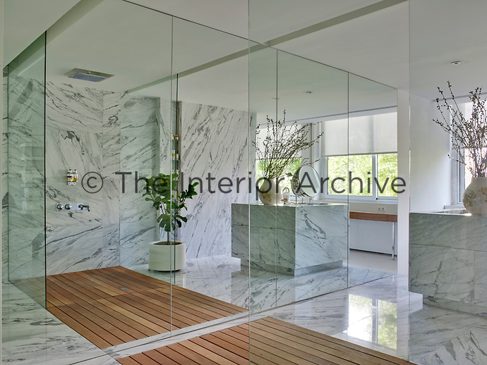 Grey-veined marble has been used in the bathroom for floors, walls and a sculpted sink unit, while a mirrored wall helps circulate light and increase the sense of space