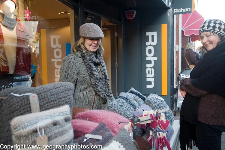 Textile stall with female stall holder and woman customer street fair, Woodbridge Suffolk, England