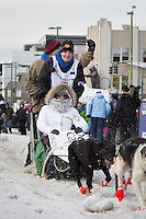 Christine Roalofs and team leave the ceremonial start line with an Iditarider at 4th Avenue and D street in downtown Anchorage, Alaska during the 2015 Iditarod race. Photo by Jim Kohl/IditarodPhotos.com