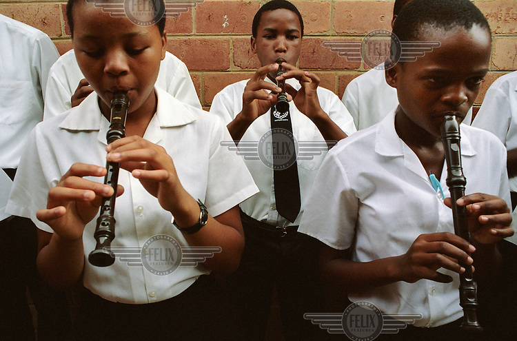 Pupils play recorders during a music lesson at Zwelibanzi High School in Umlazi Township. .