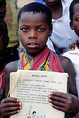 Ninde, Tanzania. Child in colourful cotton print wrap dress holding a book written in Swahili.