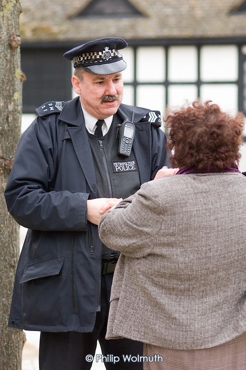 Police and residents talk at the opening of re-paved open space in Church Street, Paddington, London.