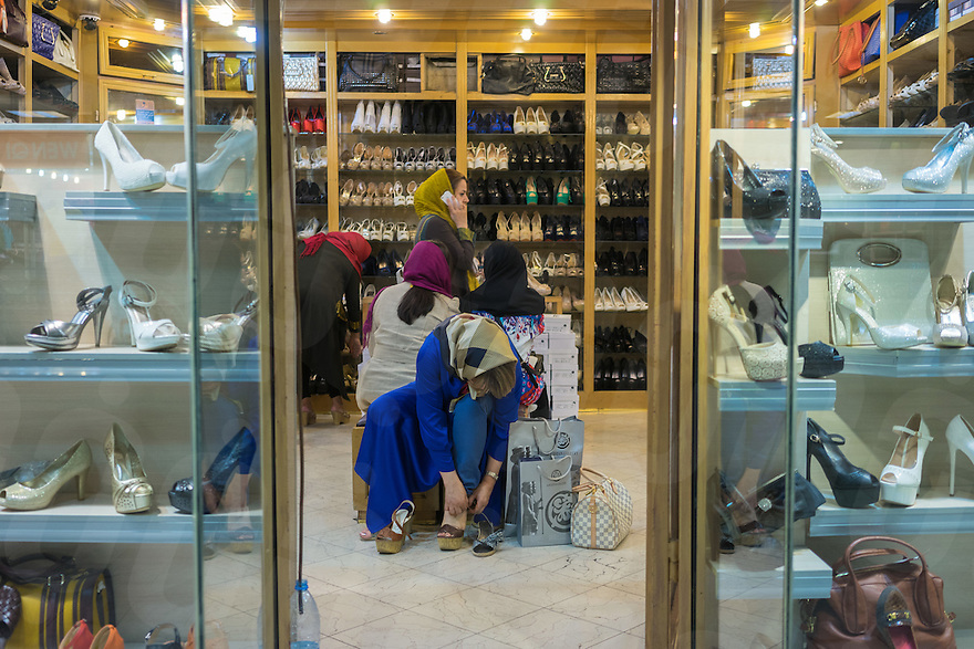 June 09, 2014 - Tehran, Iran. A young girls try on a pair of shoes in a shop at Golestan Shopping Center, one of the first mall built in the country. © Thomas Cristofoletti / Ruom