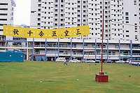 Singapore. Downtown. Town center. Chinatown. A chinese gardener uses a plastic bag to collects rubbish on  the grass near high-rise buildings The tower blocks are Housing Developping Buildings (HSB). A sign in chinese writing floats in the wind.  © 2001 Didier Ruef