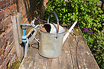 Old metal watering can and tap in gardens at Helmingham Hall, Suffolk, England