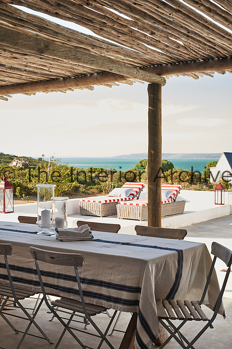 A table and chairs on a covered terrace with a view looking out to sea