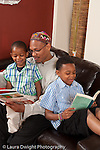 father at home reading book to 3 year old son with 8 year old son reading to himself in the background vertical