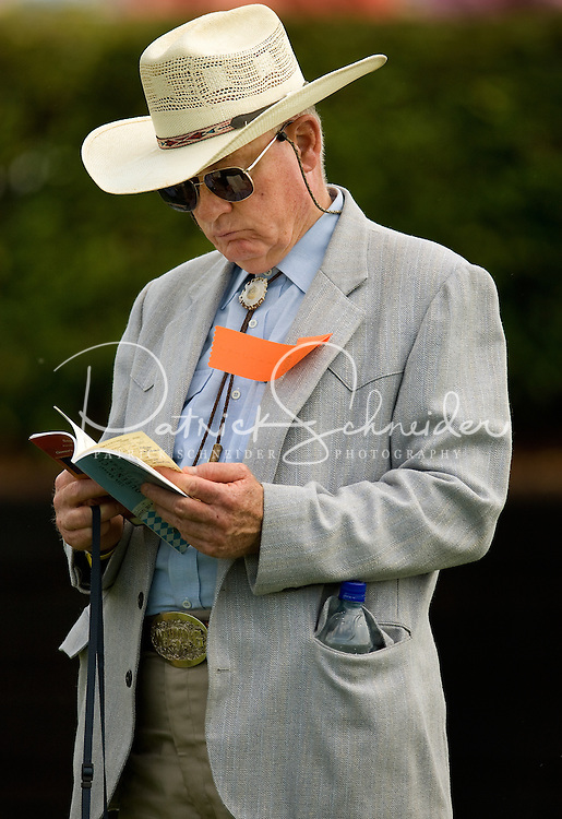 A man looks over the program during the Queen's Cup Steeplechase in Mineral Springs, NC.