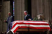 Former President George W. Bush puts his hand on the flag-draped casket of former President George H.W. Bush after giving a eulogy during the State Funeral at the National Cathedral, Wednesday, Dec. 5, 2018, in Washington. <br /> Credit: Alex Brandon / Pool via CNP