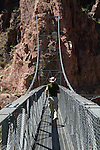Runner on the Silver Bridge over the Colorado River at Phantom Ranch Campground, Grand Canyon, Arizona. . John offers private photo tours in Grand Canyon National Park and throughout Arizona, Utah and Colorado. Year-round.