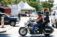 NWA Media/DAVID GOTTSCHALK - 9/22/14 - Set up work continues Bikes, Blues & BBQ venue in the Walton Arts Center parking lot on Dickson Street and West Street as motorcycle traffic pass by Monday September 22, 2014 in Fayetteville. This is the 15th year for the motorcycle rally that runs from September 24 through September 27 with music, vendors, activities and events taking place throughout Fayetteville and Northwest Arkansas.