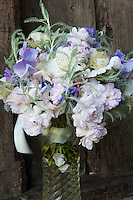 A vase of roses and sweet peas in pale purples and whites