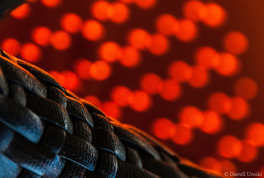 Abstract artistic photograph of the sun casting bright red coloured circles of light on to the fabric of a chair.