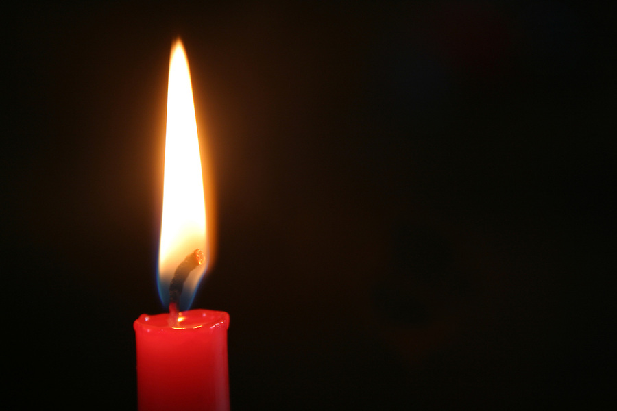 Red candle lit against black background
