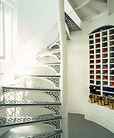 A wrought-iron spiral staircase winds its way up the whitewashed brick tower and a collection of neatly folded flags is stored in a series of pigeon holes on the ground floor