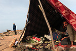 An Egyptian man looks out from a shelter made out of blankets and tree branches on the Tunisian side of the Ras Jidir border crossing with Libya, March 3, 2011. More than half of the 180,000 people estimated to have fled Libya have crossed into Tunisia. Thousands of Egyptian, Bangladeshi and Sri Lankan migrant workers are stuck at the border as aid organizations and governments struggle to get them home via an airlift operation.