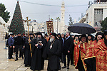 Clergymen walk as Jerusalem's Greek Orthodox patriarch Theophilos III arrives to attend a Christmas service according to the Eastern Orthodox calendar, in the church of Nativity in the West Bank town of Bethlehem on January 6, 2018. The municipalities of Bethlehem, Beit Sahour and Beit Jala, all in the Israeli-occupied West Bank, called for the boycott over Jerusalem's Greek Orthodox patriarch allegedly allowing controversial real estate sales. Photo by Wisam Hashlamoun