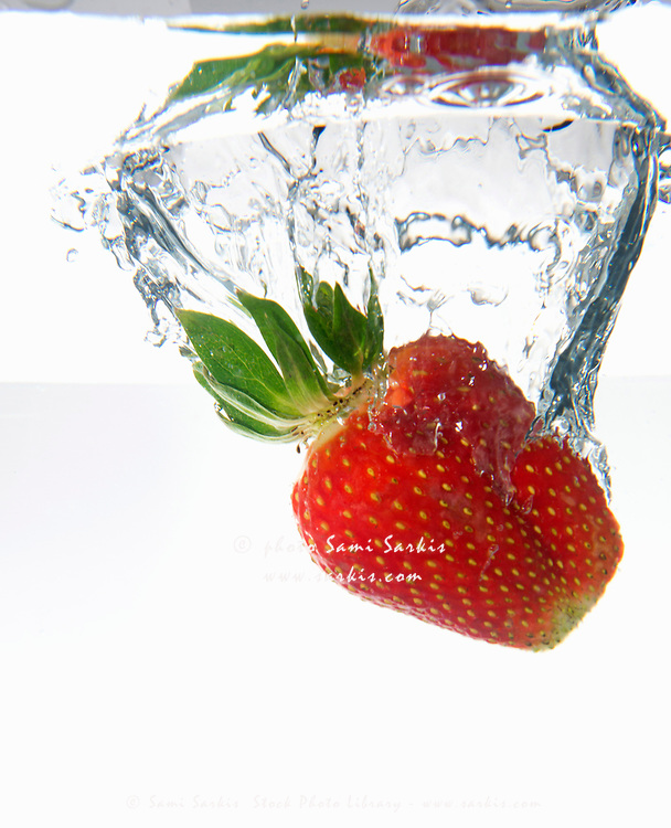 One strawberry fruit splashing underwater, white background, studio