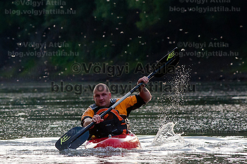 Kayaker paddles during the yearly few days long swarming of the long-tailed mayfliy (Palingenia longicauda) on the river Tisza in Tiszainoka (some 135 km south-east from Budapest), Hungary on June 12, 2011. ATTILA VOLGYI.The long-tailed mayfly larves live 3 years under water level in the river banks then swarm out for a one day period of their life to die after mating.
