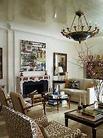 In the living room, a luminous glow is cast onto the Venetian plaster walls by the aluminium-leaf ceiling. The custom-made sofa is covered in a Kravet chenille, the armchairs are upholstered in a Rogers & Goffigon fabric and the club chairs are in a leopard print by Tafford Fabrics. The 1940s cocktail table is attributed to Jacques Quinet. Above the fireplace, a painting by Canan Tolon is flanked by 19th century Italian mirrors.