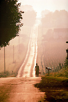 At sunset an Amish girl walks from school with lunch box on a long country road. Amish youth. Ohio.