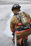 firefighter fire emergency safety person 911 alertness anticipation assistance government city life confidence courage brave crisis dedication call male man teamwork dependence masculinity pride job career occupation department rescue risk news service security strength team toughness  hoseline water ready readiness exercise uniform gear