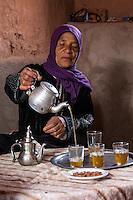 Morocco.  Amazigh Berber Woman Pouring Tea, Ait Benhaddou Ksar, a World Heritage Site.
