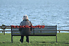 A woman sits on a bench at East Beach in Shoeburyness in Essex, UK.